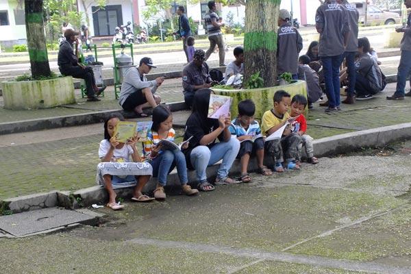 Anak-anak membaca buku yang disedikan komunitas Ngampar Boekoe. (Foto: Asep Purnama)